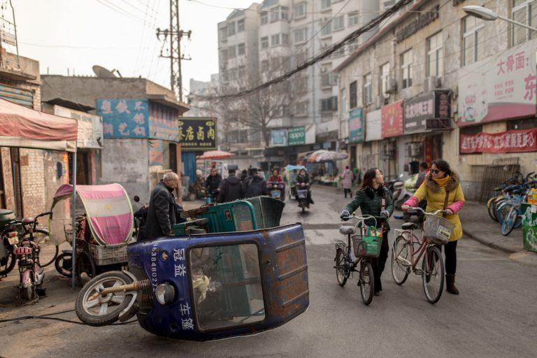 Auf einer Straße in einem Viertel in Luoyang repariert ein Mann sein motorisiertes Transportdreirad. Luoyang - Henan - China