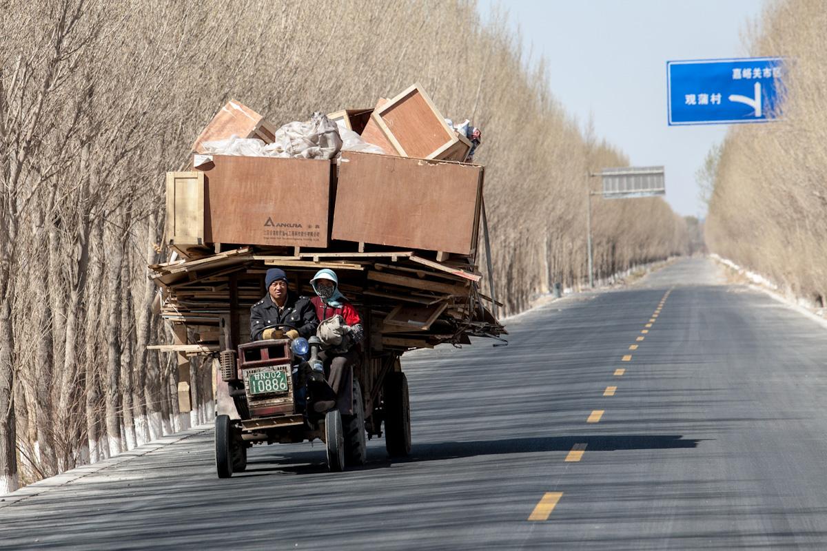 Eine Familie fährt mit ihrem Traktor und vollbeladenem Anhänger, der nach allen Seiten übersteht, auf der Landstraße nach Xinchengzhen. Das Dorf liegt in der Umgebung von Jiayuguan, im Nordwesten Chinas. Xinchengzhen - Gansu - China