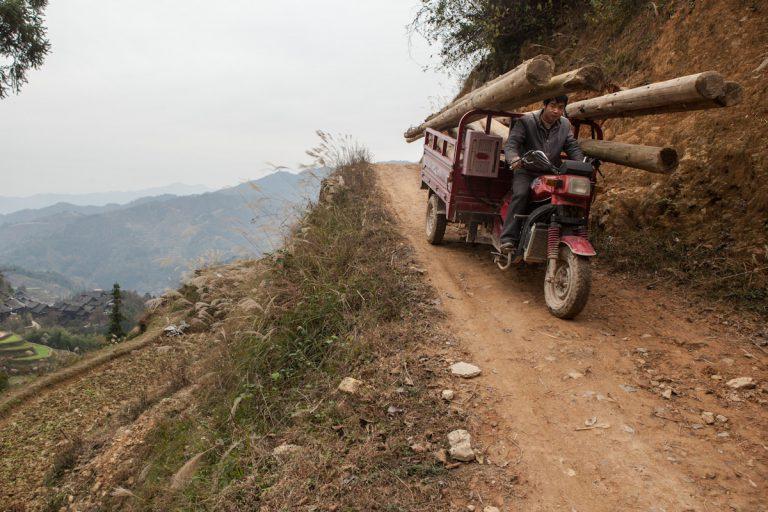 Ein Mann fährt mit seinem Motorrad, beladen mit großen Holzpfosten, einen steilen Weg hinunter. Das Dorf Jiluncun liegt im autonomen Bezirk Qiandongnan der Miao und Dong im Südosten der chinesischen Provinz Guizhou. Jiluncun - Guizhou - China