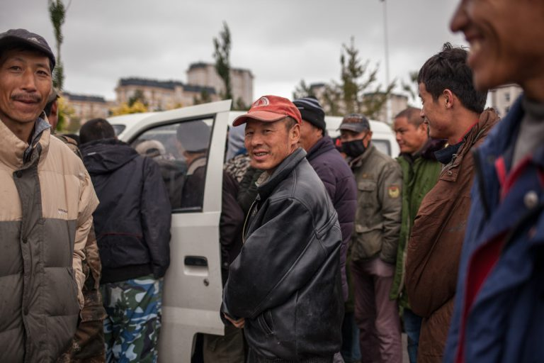 Die Männer sprechen mit einem anderen Mann in einem Auto, der Arbeiter für eine Tagesarbeit sucht. Hulun Buir - Innere Mongolei - China