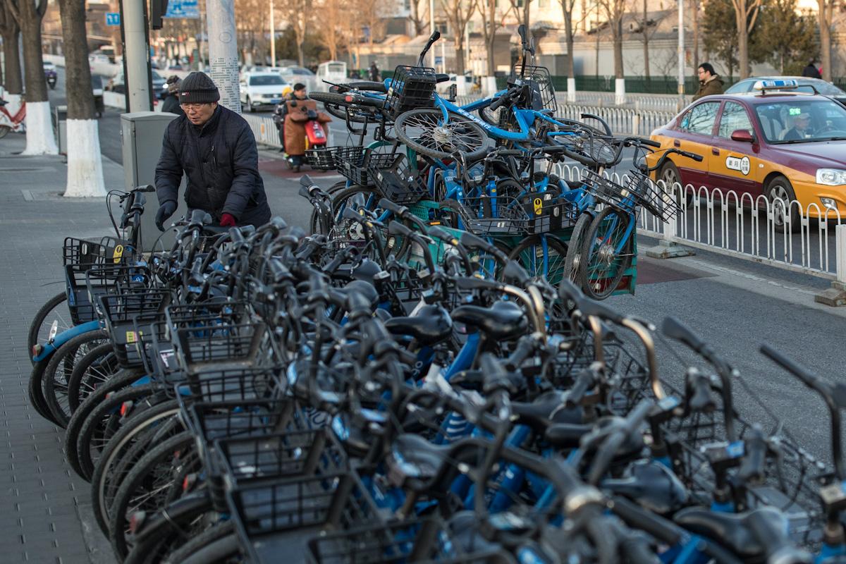 Ein Mitarbeiter eines Fahrradverleihers lädt Fahrräder auf einen Anhänger, an dem zu viele davon stehen. Peking - China