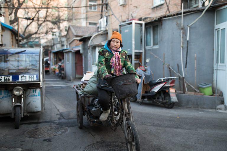 Eine Frau fährt mit ihrem beladenen Dreirad eine Straße in einem Hutong entlang. Peking - China