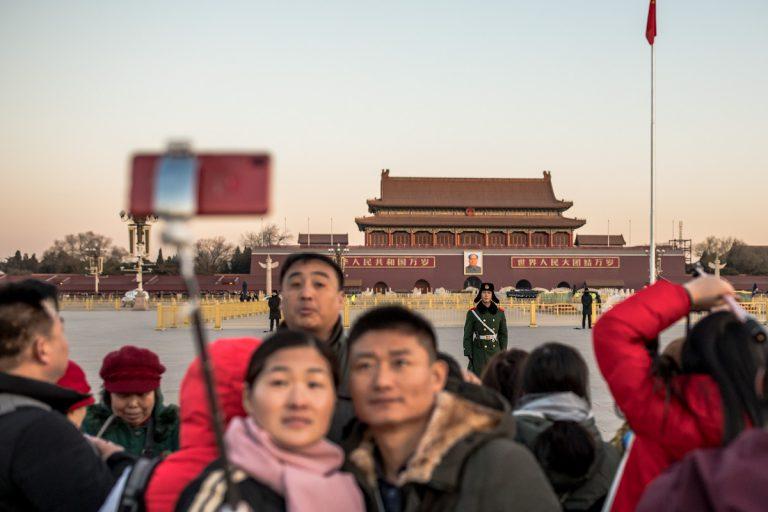 Eine Paar fotografiert sich nach der Zeremonie zum Hissen der Nationalflagge auf dem Platz des Himmlischen Friedens. Im Hintergrund befindet sich das Tor des Himmlischen Friedens. Peking - China