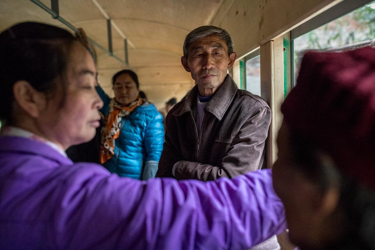 Einheimische fahren mit einem lokalen kohlebetriebenen Dampfzug. Yuejin Bagou - Sichuan - China