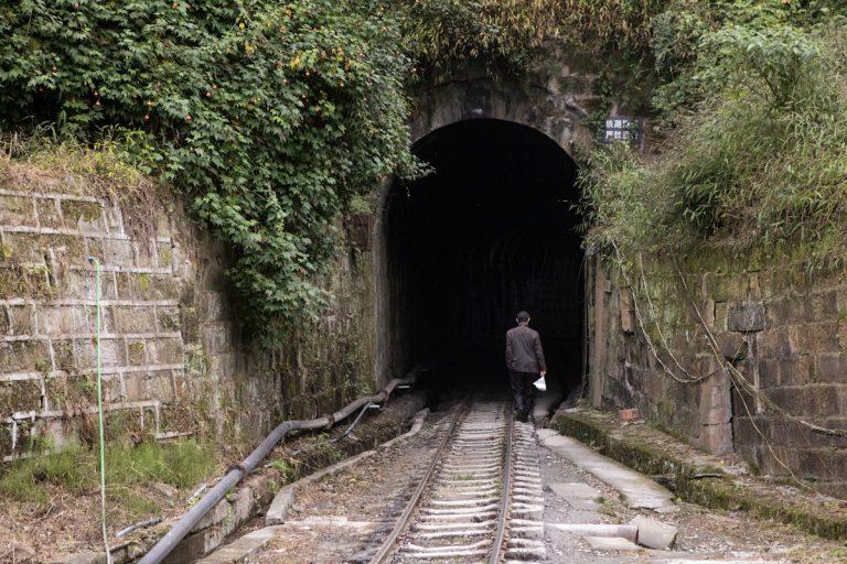 Ein Anwohner nutzt den Tunnel auf der Bahnstrecke in der Nähe von Bagou. Yuejin Bagou - Sichuan - China