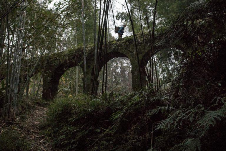 Ein Mann überquert auf einem Viadukt ein kleines Tal in der Umgebung von Bagou. Yuejin Bagou - Sichuan - China