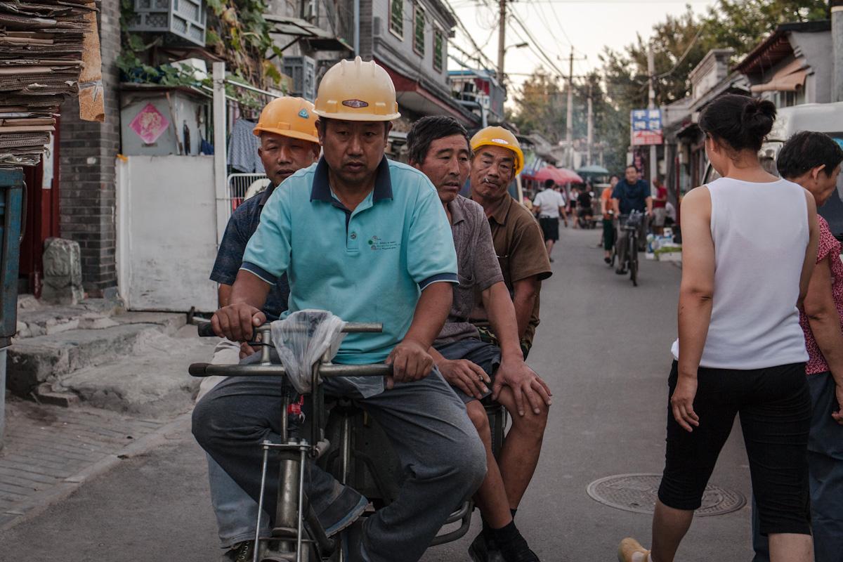 Mehrere Arbeiter fahren am Abend auf einem Moped durch ein Hutong, nahe der Verboteten Stadt. Peking - China