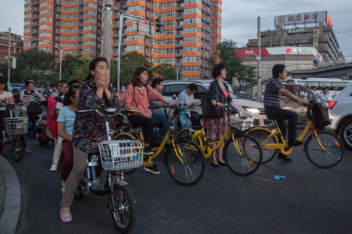 An einer Kreuzung warten Radfahrer auf ihrem abendlichen Weg, dass sie weiterfahren können.