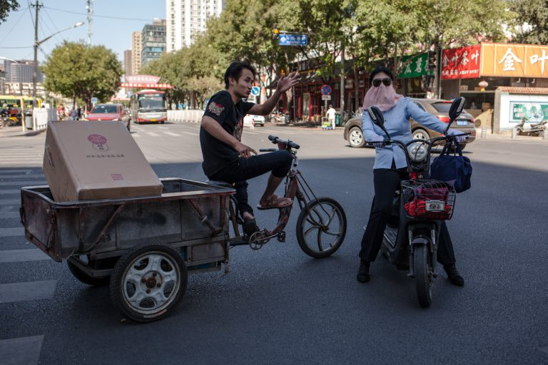 An einer Kreuzung fragt eine Frau auf einem Moped einen Mann auf einem Dreirad nach dem Weg. Mit einem Tuch vor dem Gesicht schützt sie sich vor der Hitze und Sonne. Pekig - China