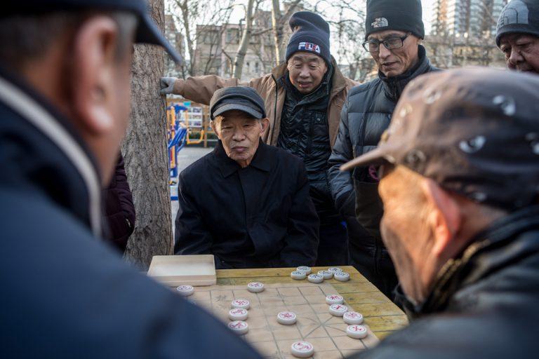Vor einem Wohnhaus spielen an einem Wintertag mehrere Männer Xiangqi, das chinesische Schach. Peking - China